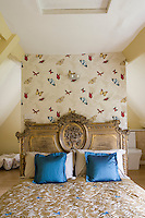 A double bed with carved wooden headboard against butterfly print wallpaper concealing the bathroom behind