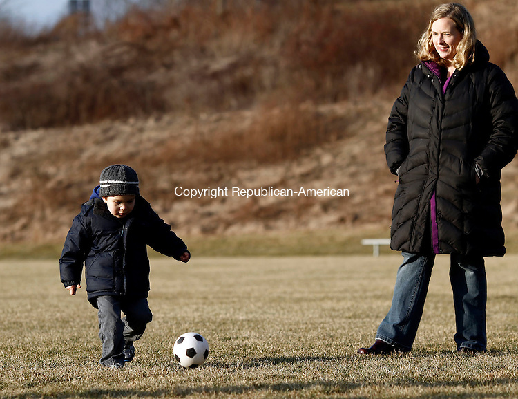 Middlebury, CT- 17 January 2014-011714CM04-  Nate Davis, 4, of Lexington, MA kicks the soccer ball at Meadowview Park in Middlebury on Friday.  Looking on is mom, Jamie Davis.  Along with Nate's sister,  Charlotte, 21 months, they were visiting their grandfather Jim Levine, of Middlebury and were enjoying the milder weather by kicking around the soccer ball.    Christopher Massa Republican-American