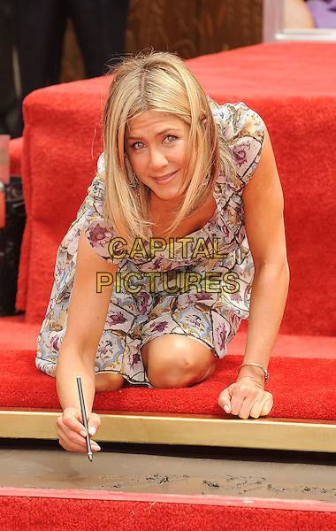 Jennifer Aniston.The Jennifer Aniston Hand and Footprints Ceremony held at The Grauman's Chinese Theatre in Hollywood, California, USA..July 7th, 2011.full length white grey gray purple floral print dress kneeling .CAP/ROT/TM.©Tony Michaels/Roth Stock/Capital Pictures