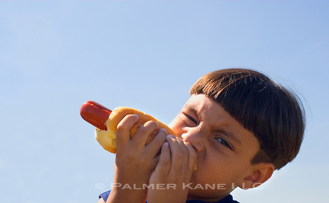 Little boy eating big juicy hot dog