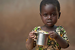 Three-year old Janesi Manuel, whose family was displaced by armed conflict, holds a cup of porridge in a camp for internally displaced persons that formed around the Our Lady of Assumption Catholic Church in Riimenze, South Sudan. The food is part of an emergency response by the parish and Solidarity with South Sudan, an international network of Catholic groups supporting education and humanitarian work in the war-torn African country.