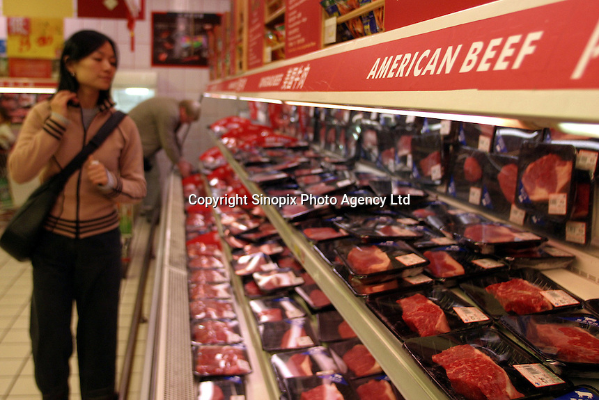 A Chinese shopper looks at beef products at a supermarket in Shanghai, China. Fearing the most recent mad cow disease case from the United States, China has banned beef imports from the U.S..27-DEC-03