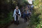 Old Mans Day Braughing Hertfordshire October 2nd. 2015. The vicar the Rev'd Julie Gawthrope sweeping Fleece Lane from the Fleece Inn leading to St Marys the Virgin church with the help of children from Jenyns First School.