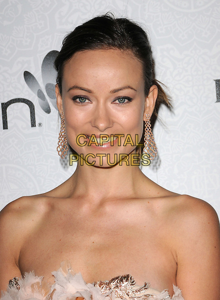 "OLIVIA WILDE.Art of Elysium 3rd Annual Black Tie charity gala '""Heaven"" held at 990 Wilshire Blvd in Beverly Hills, California, USA, .January 16th 2010 .headshot portrait dangly earrings strapless beige cream nude gold hair up feathers feather smiling .CAP/RKE/DVS .©DVS/RockinExposures/Capital Pictures"
