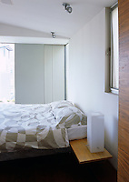 View into a simple contemporary bedroom with a small bedside table attached to the bed