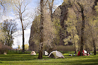 Tents are set up below cottonwood trees at Barretts Division Dam on the Beaverhead River near Dillon, Montana.