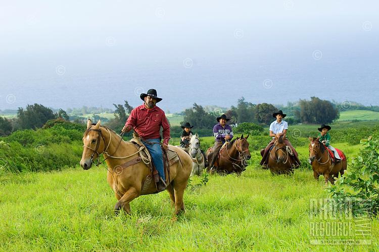Hawaiian cowboys (paniolos) and their children riding on a Big Island ranch.