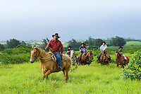 Hawaiian cowboys (paniolos) and their children riding on a Big Island ranch.