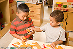 Preschool ages 3-5 two boys playing with play dough boy sharing giving piece to the other boy horizontal