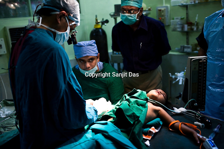 Micro hand surgeon, Dr. Pankaj Jindal (left) conducts corrective surgery to a young child at the local hospital in Chalisgaon, Maharashtra, India. Rotary Club organises a free medical camp for the poor and needy. India's leading Micro and plastic surgeons visit the medical camp and provide free medical service.