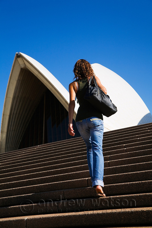 A woman walks the steps of the Sydney Opera House.  Sydney, New South Wales, AUSTRALIA.