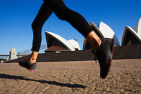 The Sydney Opera House is framed by the legs of an early morning jogger.  Sydney, New South Wales, AUSTRALIA.