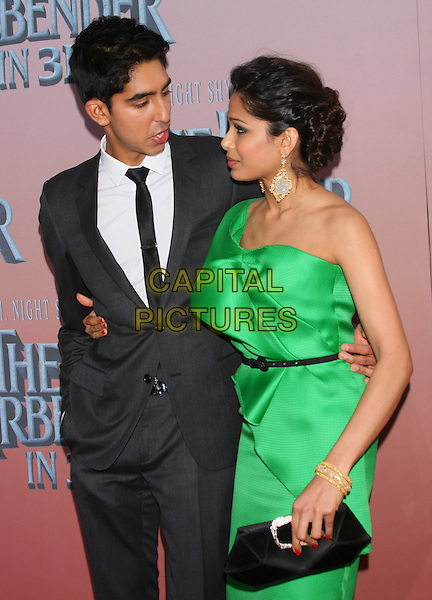 "DEV PATEL & FREIDA PINTO  .The World Premiere of ""The Last Airbender"" at Alice Tully Hall @ Lincoln Center, New York, NY, USA..June 30th, 2010.half length green silk satin dress one shoulder couple black waist belt suit tie white shirt arm around clutch bag  profile earrings gold mouth open bracelets .CAP/LNC/TOM.©TOM/LNC/Capital Pictures."