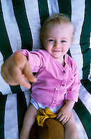 One year old baby girl pointing and smiling.