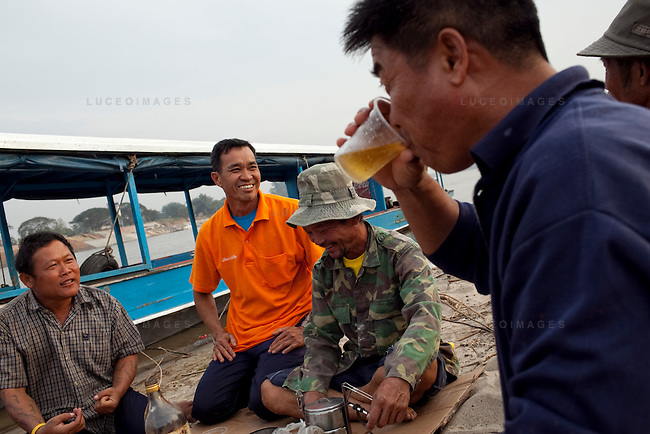 """Thai tour boat operators from left, Mon, Peng, Noi, and Bounsri drink Lao beer and whiskey on a beach in Myanmar on the Mekong River near Sop Ruak, Thailand. """"Some times business is not good because the water is low from the dams in China that we have to take boats out,"""" Noi said. Photo taken on Thursday, December 10, 2009. Kevin German / Luceo Images"""