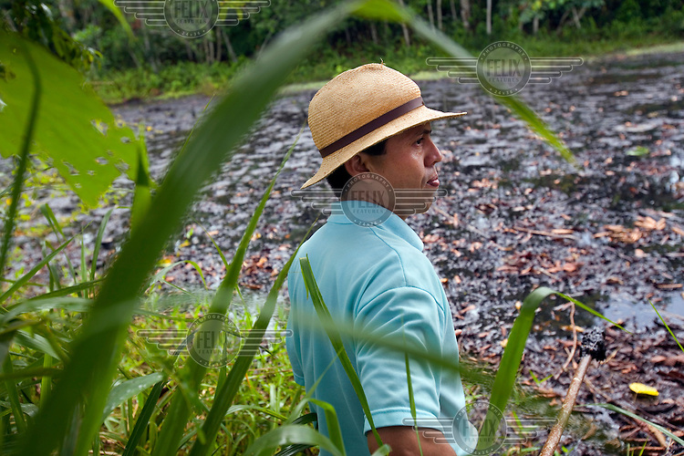 Pablo Fajardo stands in front of a pool of crude oil and waste left by Texaco at well Shushufindi 61. He is the lead attorney for plaintiffs in a class action lawsuit brought against US multinational Texaco (acquired by Chevron in 2001) by more than 30,000 Ecuadorians. The case has been in the Ecuadorian courts since 2003 and relates to the dumping of billions of gallons of toxic materials into unlined pits and Amazonian rivers. In February 2011 the court ruled that Chevron should pay a fine totalling 9.5 billion USD. However, Chevron has stated that the ruling is 'illegitimate and unenforceable' and has started numerous counter proceedings in US courts. There is some doubt as to whether it will be possible to force Texaco to pay the fine.