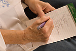 "closeup of hands of senior woman in late 70s writing ""to do"" list on pad horizontal"