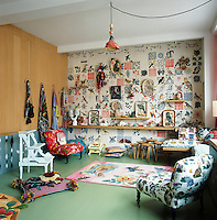 The sitting room has a feature wall comprising a striking piece of tiled artwork. Other art pieces by the owner, Nathalie Lété, are displayed around the room