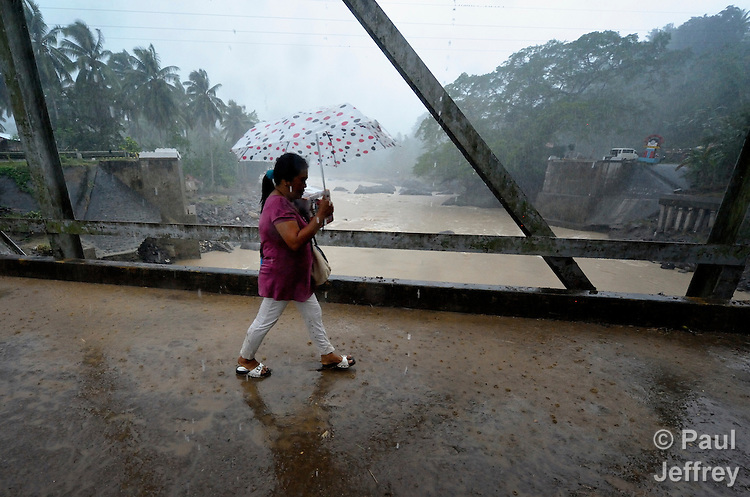 The day after Typhoon Bopha raged through the southern Philippines island of Mindanao, a woman walks across a small footbridge over the Cagayan River at Uguiaban. The main bridge for a regional highway--which once spanned the river in the background, collapsed during the flooding.