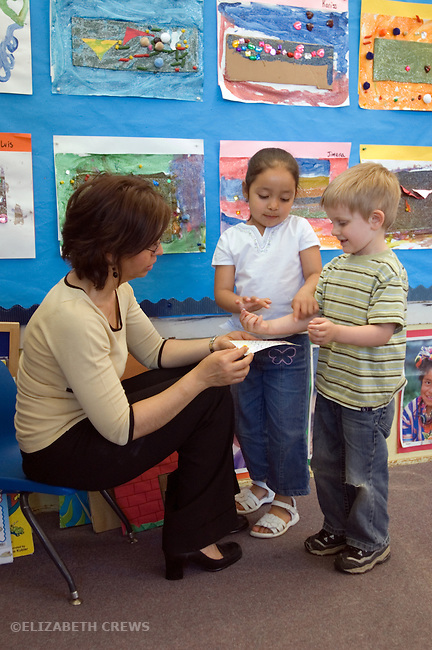 Berkeley CA  Preschool teacher handing out performance starts to students as they prepare to go home.