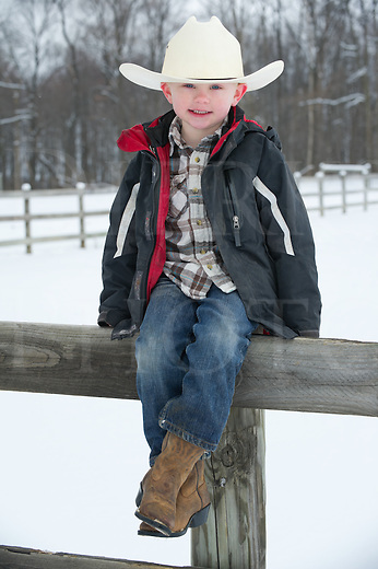 Young boy sitting on fence enjoying himself with Appaloosa horse, five years old dressed in white cowboy hat, winter snow scene in Pennsylvania, PA, USA.