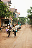VIETNAM, Hanoi, Countryside, women ride their bikes along a rural road in Thanh Bac Ninh