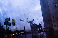 A statue of the bull are seen through a rainy car window during the early evening twilight in Quito, Ecuador, 12 November 2012.