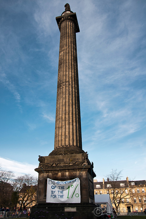 "The Melville Monument at St Andrew's Square, Edinburgh, with a banner from the Occupy Edinburgh Monument reading ""End Government of the 1% by the 1% for the 1%""."