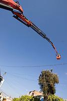 Quer&eacute;taro, Qro. 15 enero 2014.- Trabajadores del municipio de Quer&eacute;taro, realizan poda de &aacute;rboles en la calle de Artes, en el tradicional Barrio de San Francisquito. Para llegar a las alturas, utilizan una gr&uacute;a de canastacon la que adem&aacute;s de llegar a la copa del &aacute;rbol, logran evitar los cables de alta tensi&oacute;n.  <br /> <br /> <br /> Foto: Demian Ch&aacute;vez / Obtura Press Agency.
