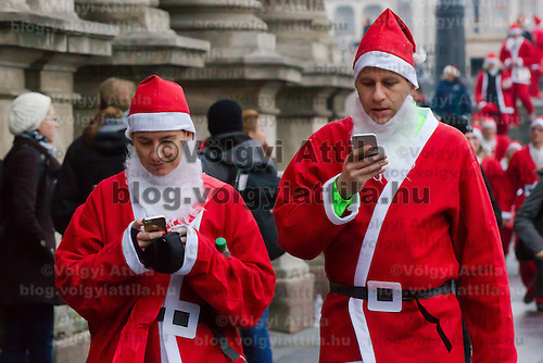 Participants in Santa Claus costume use their phone after the first ever mass Santa Run in central Budapest, Hungary on December 06, 2014. ATTILA VOLGYI