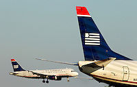 One US Airways jet lands as another plane waits to take off at Charlotte-Douglas International Airport in Charlotte, North Carolina. Charlotte-based photographer has other images of transportation, airplanes on runways (and taking off and landing) and interior/exterior airport images of Charlotte-Douglas Intl Airport in portfolio.