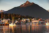 USA, Alaska, Sitka, a peaceful view of homes and fishing boats along the shore in Sitka Harbor at sunset, Mount Verstovia peak in in the distance