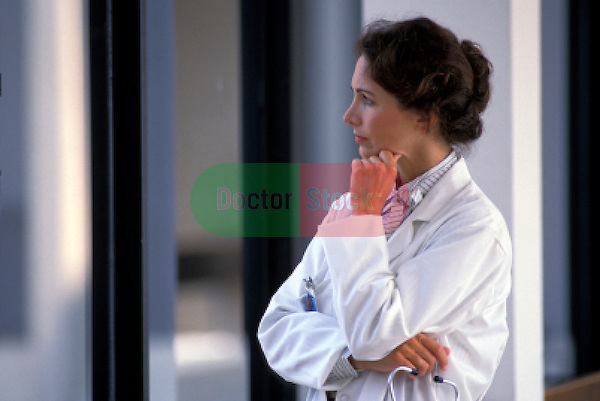 woman doctor in hospital corridor deep in thought