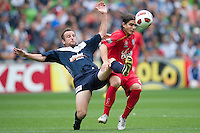 MELBOURNE, AUSTRALIA - JANUARY 09: Francisco Usucar of United holds off the challenge by Grant Brebner of the Victory during the round 22 A-League match between the Melbourne Victory and Adelaide United at AAMI Park on January 9, 2011 in Melbourne, Australia. (Photo by Sydney Low / Asterisk Images)