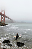 USA, California, San Francisco, a surfer gets ready to paddle out to catch some waves at Fort Point beneath the Golden Gate Bridge