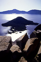 Silhouette of Crater Lake and its cone. Scenic image with sharp rocks in the foreground