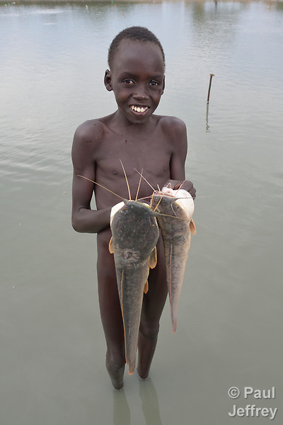 Marial Majak, 13, displays fish he caught in Poktap, a town in South Sudan's Jonglei State where conflict, drought and inflation have caused severe food insecurity. <br />