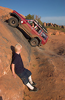 """Jeremy Christensen, 6, of Moab, Utah, watches as Kurtis Houston, of Grand Junction, Colo., attempts to climb the """"Dump Bump,"""" a challenging sandstone step above Moab, Utah, Friday, April 15, 2005. After a uranium mining bust in the early 1980s, Moab has reinvented itself as a recreation mecca, attracting conflicting groups of mountain bikers, off-road drivers, climbers, hikers and rafters. (Kevin Moloney for the New York Times)"""