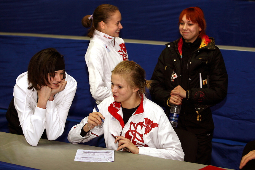 (L-R) Anna Bessonova of Ukraine, Marina Shpekt with Olga Kapranova of Russia and Natalya Godunko or Ukraine  smile while Olga completes press information form before 2006 Deriugina Cup Grand Prix event at Kiev, Ukraine on March 16.. (Photo by Tom Theobald)