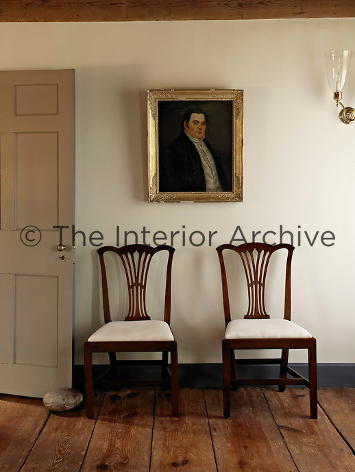 A pair of Georgian mahogany side chairs is placed beneath a formal portrait in one of the guest bedrooms