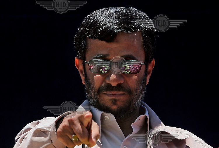 Iranian President Mahmoud Ahmadinejad points at one of his supporters in the crowd, seen partly reflected in his sunglasses, during a speech in the Iranian city of Shiraz.