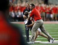 Assistant coach Anthony Schlegel grabs a fan who ran on the field during the second quarter of Saturday's NCAA Division I football game at Ohio Stadium in Columbus on September 27, 2014. (Columbus Dispatch photo by Jonathan Quilter)