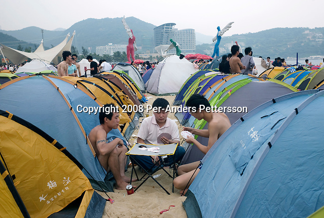 SHENZHEN, CHINA OCTOBER 2: Chinese holidaymakers play cards next to the sea at Dameisha Beach Park on October 2, 2008 outside Shenzhen, China. Millions of Chinese took a weeklong break during the National Holiday and one of the Golden weeks during the year. This is the most popular beach outside Shenzhen, and it's free. The park also has carnival rides and a statue park. Chinese people love theme parks and new ones are opening constantly. It's estimated that there's about 2400 theme parks in the country. Many of the most popular parks are located around Shenzhen and over the border in Hong Kong. (Photo by Per-Anders Pettersson)....