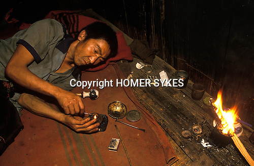 Chasing the dragon opium addict heroin Northern Thailand South east Asia.