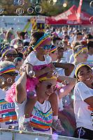 Mother giving daughter shoulder ride through bubble zone, The Color Run 2015, Tacoma, WA, USA.