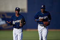 AZL Brewers Blue outfielders Terence Doston (9) and Arbert Cipion (23) jog off the field between innings of an Arizona League game against the AZL Athletics Gold on July 2, 2019 at American Family Fields of Phoenix in Phoenix, Arizona. AZL Athletics Gold defeated the AZL Brewers Blue 11-8. (Zachary Lucy/Four Seam Images)