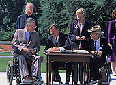 United States President George H. W. Bush signs the Americans with Disabilities Act of 1990 into law during a ceremony on the South Lawn of the White House in Washington, D.C. on July 26, 1990. Pictured (left to right): Evan J. Kemp, Jr., Chairman, U.S. Equal Employment Opportunity Commission; Reverend Harold Wilke; President Bush; Sandra Parrino; and Justin Dart.  The act prohibited employer discrimination on the basis of disability. <br /> Credit: Ron Sachs / CNP