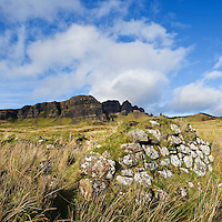 Crumbling stone wall of old croft building with the Storr in distance, Trotternish, Isle of Skye, Scotland
