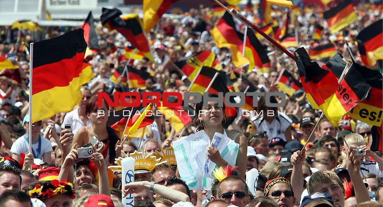 FIFA WM 2006 - Feature Fanmeile Berlin<br /> Verabschiedung / Empfang der Deutschen Nationalmannschaft auf der Berliner Fanmeile vor dem Brandenburger Tor<br /> <br /> <br /> Fans mit Deutschland-Fahnen.-- Blick vom Brandenburger Tor in die Massen<br /> <br /> Foto &copy; nordphoto