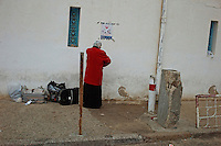 A woman standing with her belongings on the Tunisian side of the border with Libya